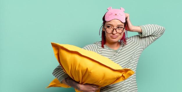Giovane donna attraente dai capelli rossi che si sente perplessa e confusa, si gratta la testa e guarda di lato e indossa un pigiama.