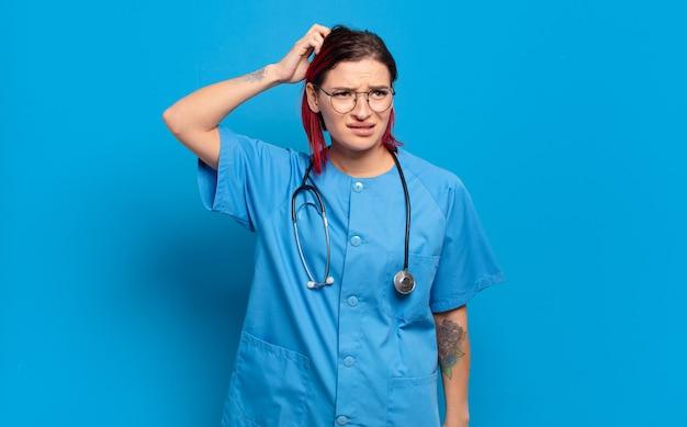 Giovane donna attraente dai capelli rossi che si sente perplessa e confusa, si gratta la testa e guarda di lato