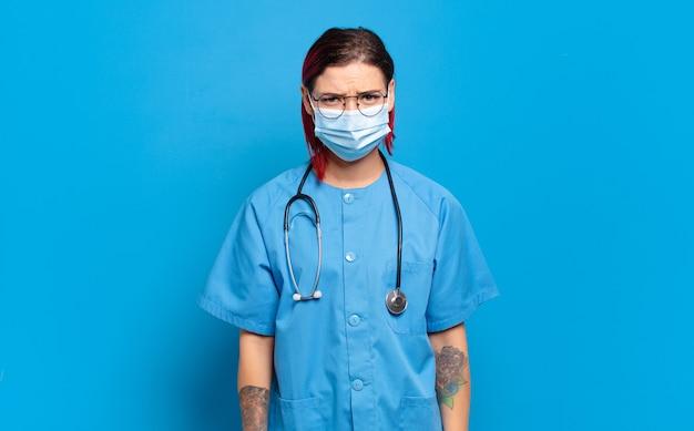 Giovane donna attraente con i capelli rossi che si sente perplessa e confusa, con un'espressione stupita e sbalordita guardando qualcosa di inaspettato. concetto di infermiera ospedaliera