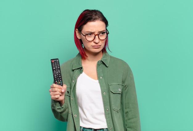 Giovane donna attraente dai capelli rossi che si sente triste, sconvolta o arrabbiata e guarda di lato con un atteggiamento negativo, accigliata in disaccordo e con in mano un telecomando della tv