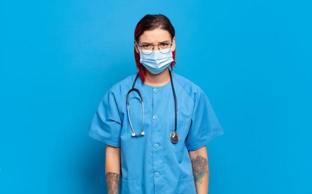 Giovane donna attraente con i capelli rossi che si sente triste e piagnucolona con uno sguardo infelice, piange con un atteggiamento negativo e frustrato. concetto di infermiera ospedaliera