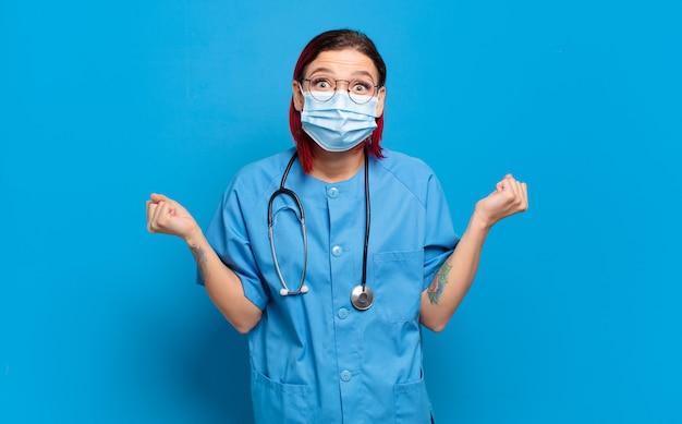 Giovane donna attraente con i capelli rossi che si sente scioccata, eccitata e felice, ridendo e celebrando il successo, dicendo wow !. concetto di infermiera ospedaliera