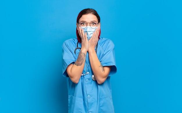 Giovane donna attraente dai capelli rossi che si sente scioccata e spaventata, sembra terrorizzata con la bocca aperta e le mani sulle guance. concetto di infermiera ospedaliera