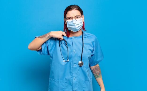 Giovane donna attraente con i capelli rossi che si sente stressata, ansiosa, stanca e frustrata, tira il collo della camicia, sembra frustrata dal problema. concetto di infermiera ospedaliera