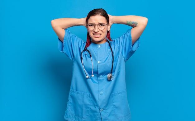Giovane donna attraente con i capelli rossi che si sente stressata, preoccupata, ansiosa o spaventata, con le mani sulla testa, in preda al panico per errore. concetto di infermiera ospedaliera