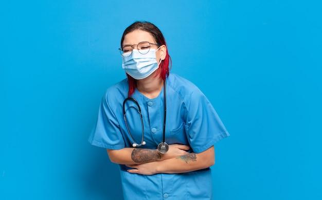 Giovane donna attraente dai capelli rossi che ride ad alta voce per qualche scherzo esilarante, sentendosi felice e allegra, divertendosi. concetto di infermiera ospedaliera