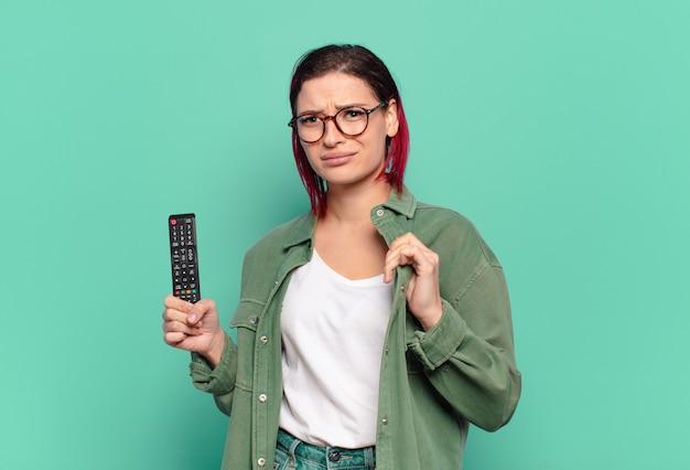 Giovane donna attraente dai capelli rossi che sembra arrogante, di successo, positiva e orgogliosa, che indica se stessa e tiene in mano un telecomando della tv