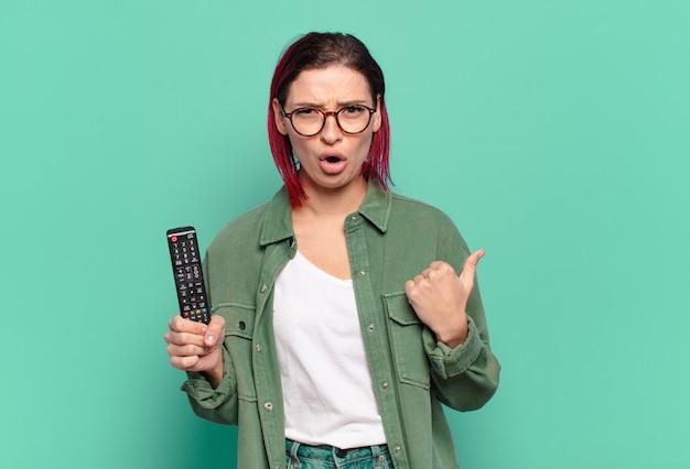 Giovane donna attraente dai capelli rossi che sembra stupita per l'incredulità, indicando l'oggetto sul lato e dicendo wow, incredibile e tenendo in mano un telecomando della tv