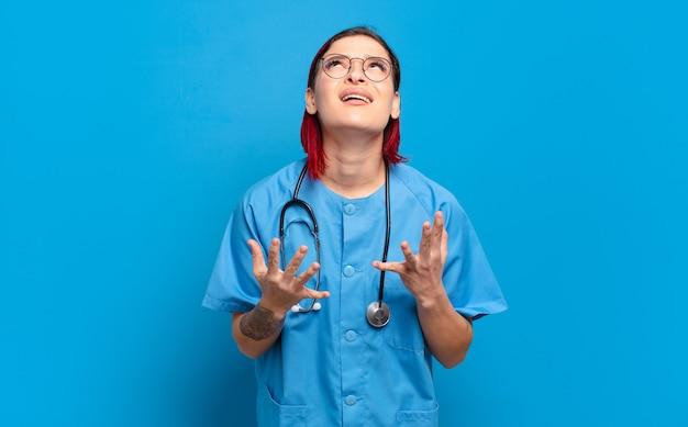 Giovane donna attraente capelli rossi che sembra disperata e frustrata, stressata, infelice e infastidita, gridando e urlando. concetto di infermiera ospedaliera