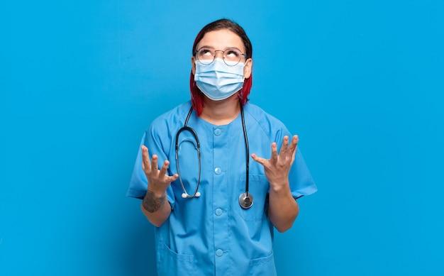 Giovane donna attraente dai capelli rossi che sembra disperata e frustrata, stressata, infelice e infastidita, urlando e urlando. concetto di infermiera ospedaliera