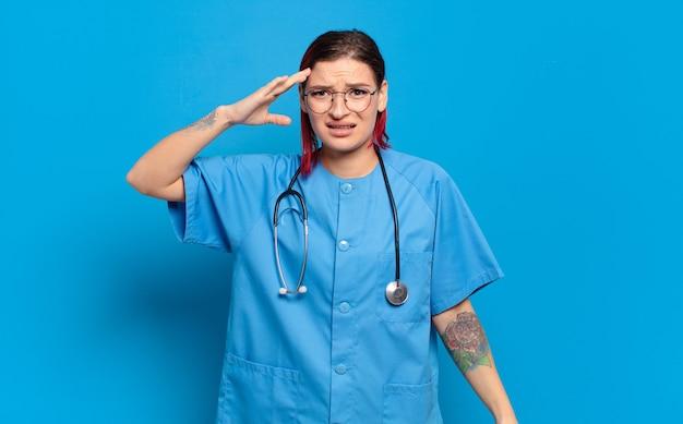 Giovane donna attraente con i capelli rossi che sembra felice, stupita e sorpresa, sorridendo e realizzando incredibili e incredibili buone notizie. concetto di infermiera ospedaliera