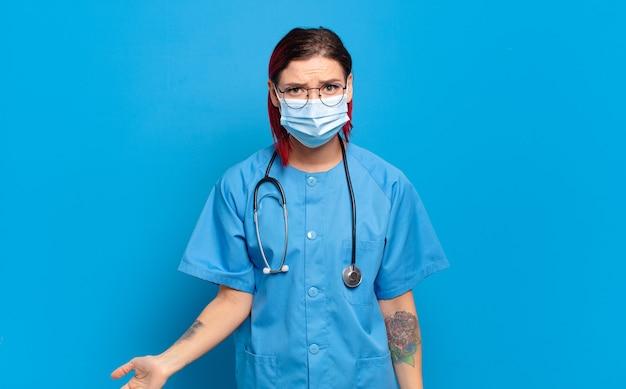 Giovane donna attraente con i capelli rossi che sembra perplessa e confusa, mordendosi il labbro con un gesto nervoso, non conoscendo la risposta al problema. concetto di infermiera ospedaliera