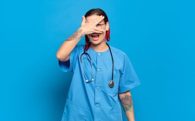 Giovane donna attraente dai capelli rossi che sembra scioccata, spaventata o terrorizzata, coprendo il viso con la mano e sbirciando tra le dita. concetto di infermiera ospedaliera
