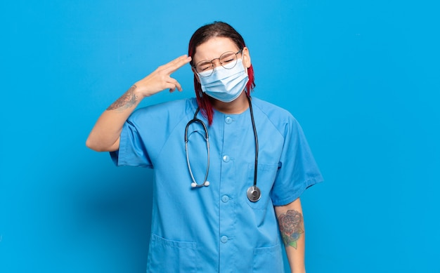 Giovane donna attraente dai capelli rossi che sembra infelice e stressata, gesto suicida che fa il segno della pistola con la mano, indicando la testa. concetto di infermiera ospedaliera