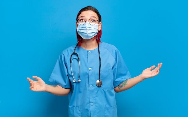 Giovane donna attraente con i capelli rossi che sembra molto scioccata o sorpresa, fissando con la bocca aperta dicendo wow. concetto di infermiera ospedaliera