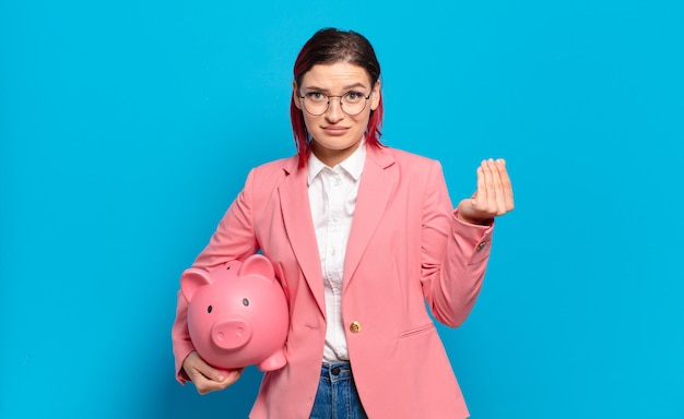 Giovane donna attraente capelli rossi che fa capice o gesto di denaro, dicendoti di pagare i tuoi debiti !. concetto di business umoristico.