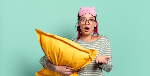 Giovane donna attraente con i capelli rossi a bocca aperta e stupita, scioccata e stupita con un'incredibile sorpresa e indossando un pigiama.