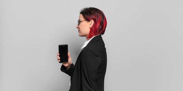 Giovane donna attraente con i capelli rossi sulla vista di profilo che cerca di copiare lo spazio davanti, pensare, immaginare o sognare ad occhi aperti. concetto di affari