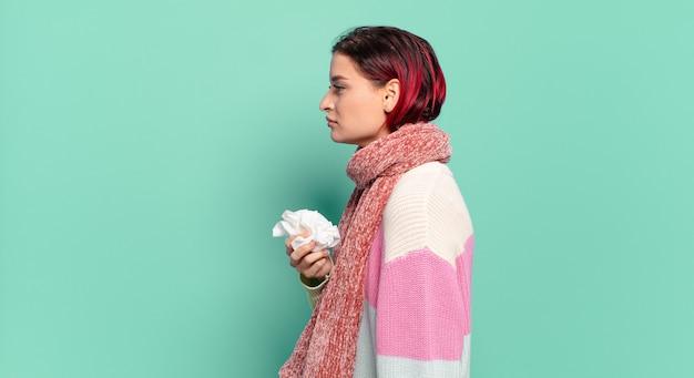 Giovane donna attraente capelli rossi sulla vista di profilo che cerca di copiare lo spazio avanti, pensare, immaginare o sognare ad occhi aperti il concetto di influenza