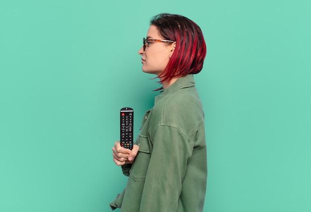 Giovane donna attraente dai capelli rossi in vista di profilo che cerca di copiare lo spazio avanti, pensando, immaginando o sognando ad occhi aperti e tenendo in mano un telecomando della tv