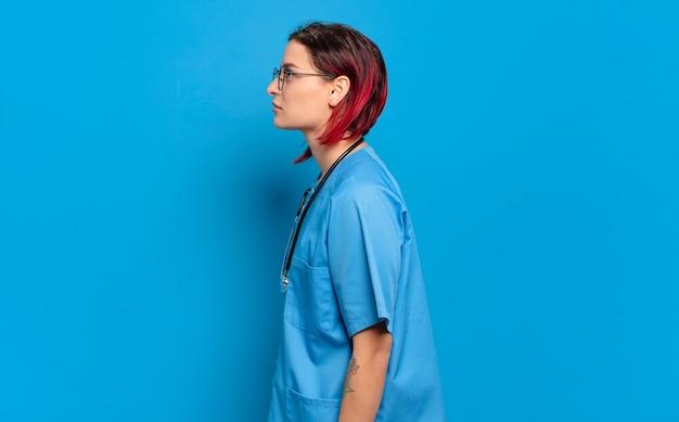 Giovane donna attraente con i capelli rossi sulla vista di profilo che cerca di copiare lo spazio davanti, pensare, immaginare o sognare ad occhi aperti