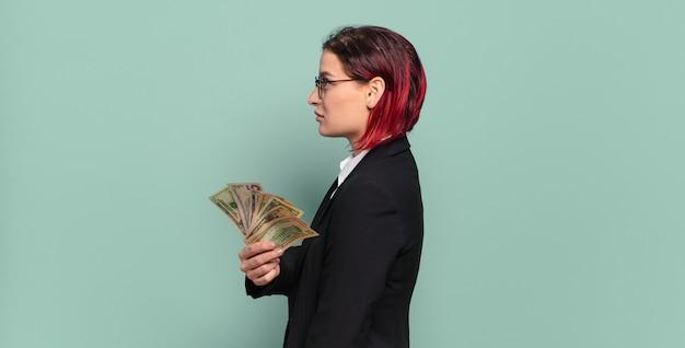 Giovane donna attraente dei capelli rossi sulla vista di profilo che cerca di copiare lo spazio avanti