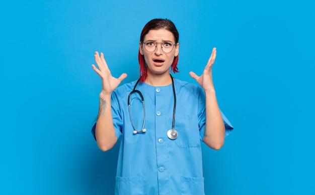 Giovane donna attraente dai capelli rossi che urla con le mani in aria, sentendosi furiosa, frustrata, stressata e turbata. concetto di infermiera ospedaliera