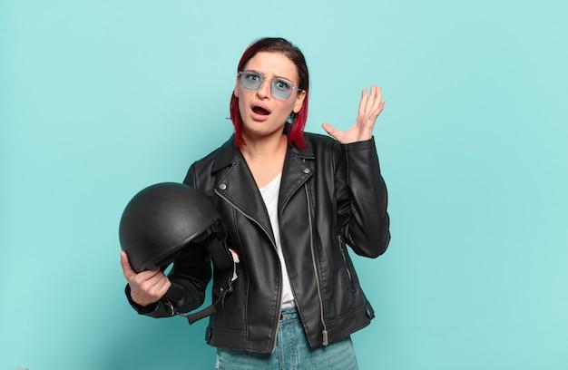 Giovane donna attraente con i capelli rossi che grida con le mani in aria, sentendosi furiosa, frustrata, stressata e sconvolta.