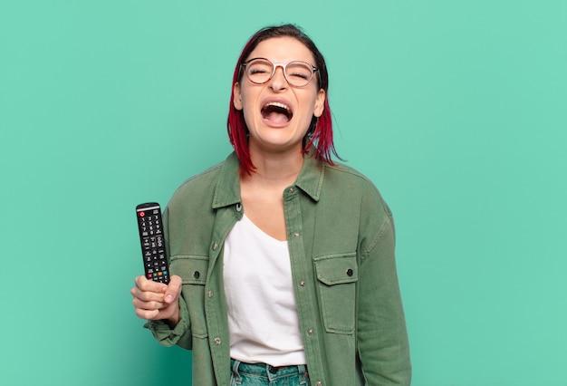 Giovane donna attraente dai capelli rossi che grida in modo aggressivo, sembra molto arrabbiata, frustrata, indignata o infastidita, urla di no e tiene in mano un telecomando della tv