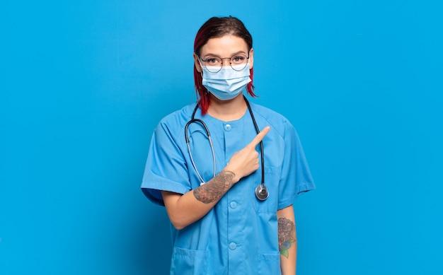 Giovane donna attraente con i capelli rossi che sorride allegramente, si sente felice e punta di lato e verso l'alto, mostrando l'oggetto nello spazio della copia. concetto di infermiera ospedaliera