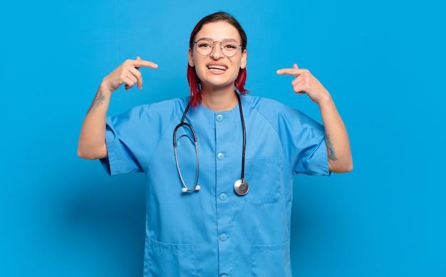 Giovane donna attraente capelli rossi che sorride fiduciosamente indicando il proprio ampio sorriso, atteggiamento positivo, rilassato e soddisfatto. concetto di infermiera ospedaliera