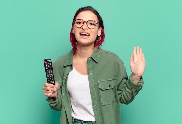 Giovane donna attraente con i capelli rossi che sorride allegramente e allegramente, agitando la mano, dandoti il benvenuto e salutandoti, o salutandoti e tenendo in mano un telecomando della tv