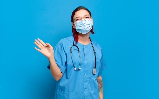 Giovane donna attraente dai capelli rossi che sorride allegramente e allegramente, agitando la mano, accogliendoti e salutandoti, o salutandoti. concetto di infermiera ospedaliera