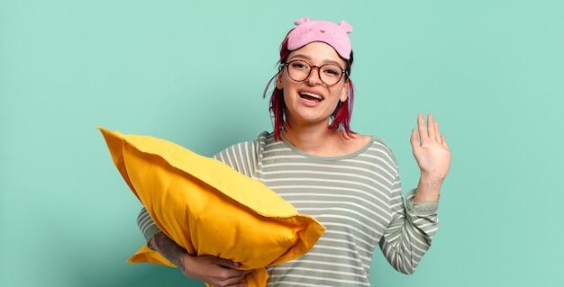Giovane donna attraente dai capelli rossi che sorride allegramente e allegramente, agitando la mano, accogliendoti e salutandoti, o salutandoti e indossando il pigiama