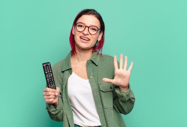 Giovane donna attraente dai capelli rossi sorridente e dall'aspetto amichevole, mostrando il numero cinque o il quinto con la mano in avanti, conto alla rovescia e tenendo in mano un telecomando della tv