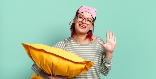 Giovane donna attraente con i capelli rossi che sorride e sembra amichevole, mostra il numero cinque o quinto con la mano in avanti, fa il conto alla rovescia e indossa il pigiama
