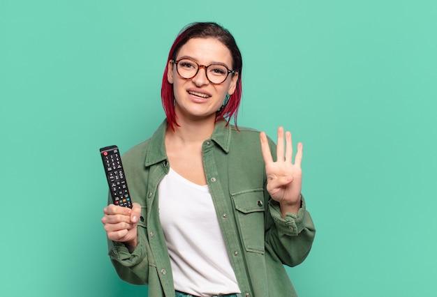 Giovane donna attraente con i capelli rossi che sorride e sembra amichevole, che mostra il numero quattro o il quarto con la mano in avanti, il conto alla rovescia e il telecomando della tv