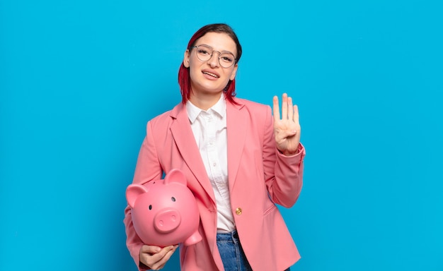 Giovane donna attraente dai capelli rossi che sorride e sembra amichevole, mostrando il numero quattro o il quarto con la mano in avanti, conto alla rovescia. concetto di business umoristico.