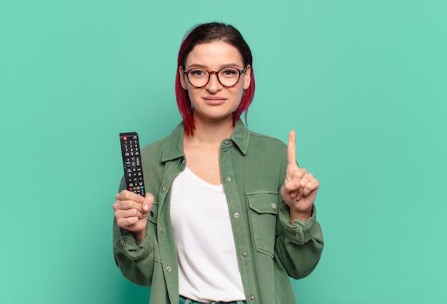 Giovane donna attraente dai capelli rossi sorridente e dall'aspetto amichevole, mostrando il numero uno o il primo con la mano in avanti, conto alla rovescia e tenendo in mano un telecomando della tv