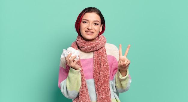 Giovane donna attraente dai capelli rossi che sorride e sembra amichevole, mostrando il numero due o il secondo con la mano in avanti, contando il concetto di influenza