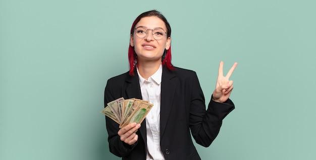 Giovane donna attraente dai capelli rossi che sorride e sembra felice, spensierata e positiva, gestualità vittoria o pace con una mano concetto di denaro