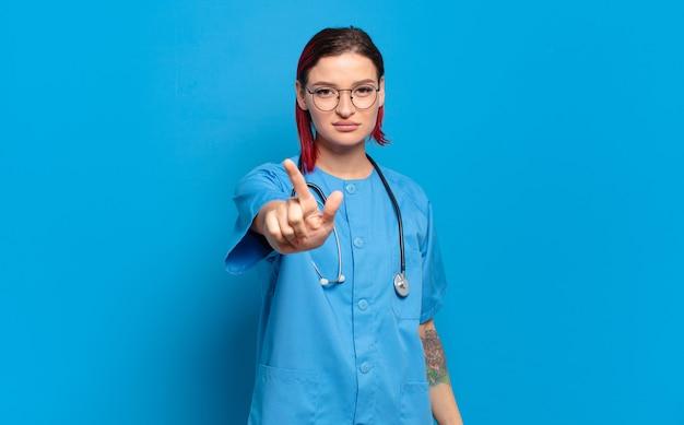 Giovane donna attraente con i capelli rossi che sorride con orgoglio e sicurezza mentre posa trionfante il numero uno, sentendosi come un leader. concetto di infermiera ospedaliera