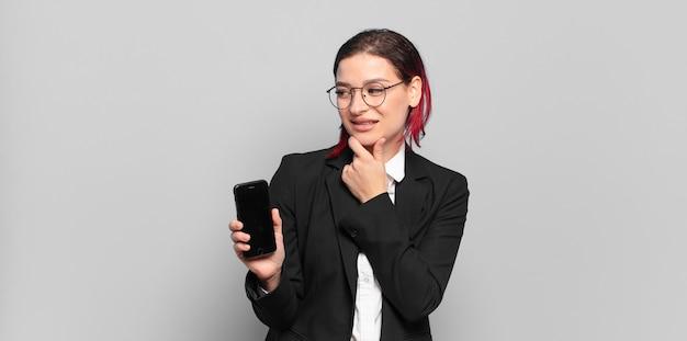 Giovane donna attraente capelli rossi che sorride con un'espressione felice e sicura con la mano sul mento, chiedendosi e guardando di lato. concetto di affari