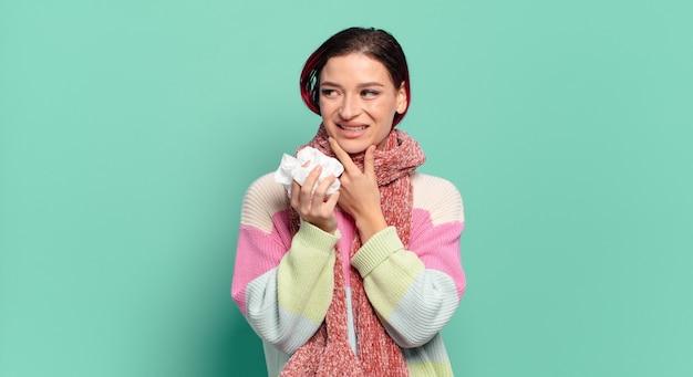 Giovane donna attraente capelli rossi che sorride con un'espressione felice e sicura con la mano sul mento, chiedendosi e guardando al concetto di influenza laterale