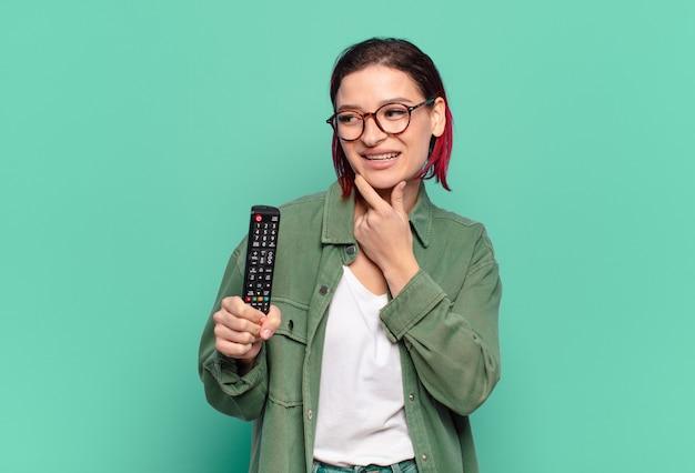 Giovane donna attraente dai capelli rossi che sorride con un'espressione felice e sicura con la mano sul mento, chiedendosi e guardando di lato e tenendo in mano un telecomando della tv