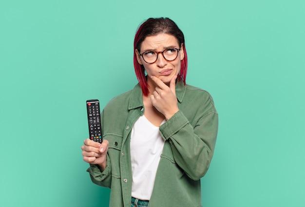 Giovane donna attraente con i capelli rossi che pensa, si sente dubbiosa e confusa, con diverse opzioni, chiedendosi quale decisione prendere e tenendo in mano un telecomando della tv