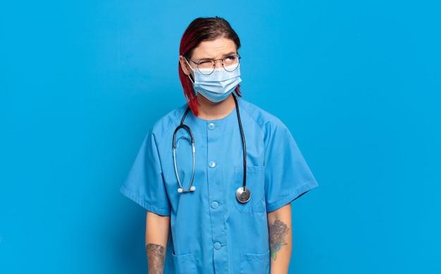 Giovane donna attraente con i capelli rossi che pensa, si sente dubbiosa e confusa, con diverse opzioni, chiedendosi quale decisione prendere. concetto di infermiera ospedaliera