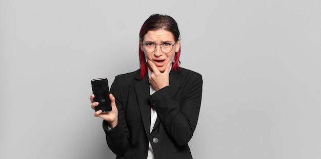 Giovane donna attraente dai capelli rossi con la bocca e gli occhi spalancati e la mano sul mento