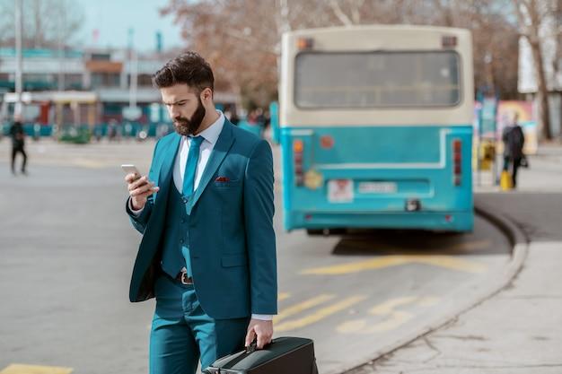 Giovane imprenditore serio attraente in tuta in piedi sul parcheggio con i bagagli in mano e utilizzando smart phone durante l'attesa sulla fermata dell'autobus.