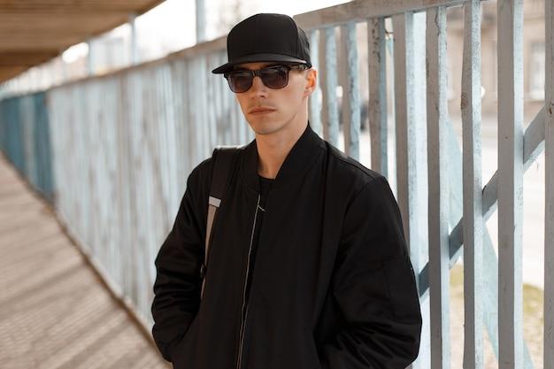 Ragazzo giovane attraente serio hipster in occhiali da sole neri in un'elegante giacca nera in un berretto nero vicino a una staccionata in legno. ragazzo americano alla moda.